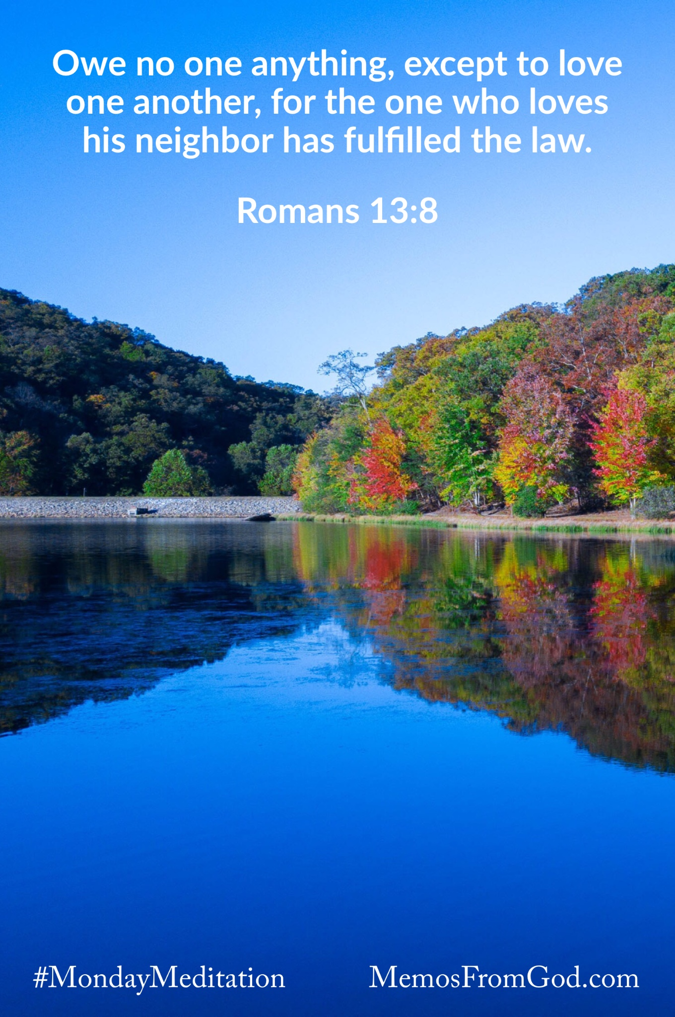 Trees with autumn coloured leaves reflecting in a deep blue lake beneath a bright blue sky. Caption: Owe no one anything, except to love one another, for the one who loves his neighbor has fulfilled the law. Romans 13:8
