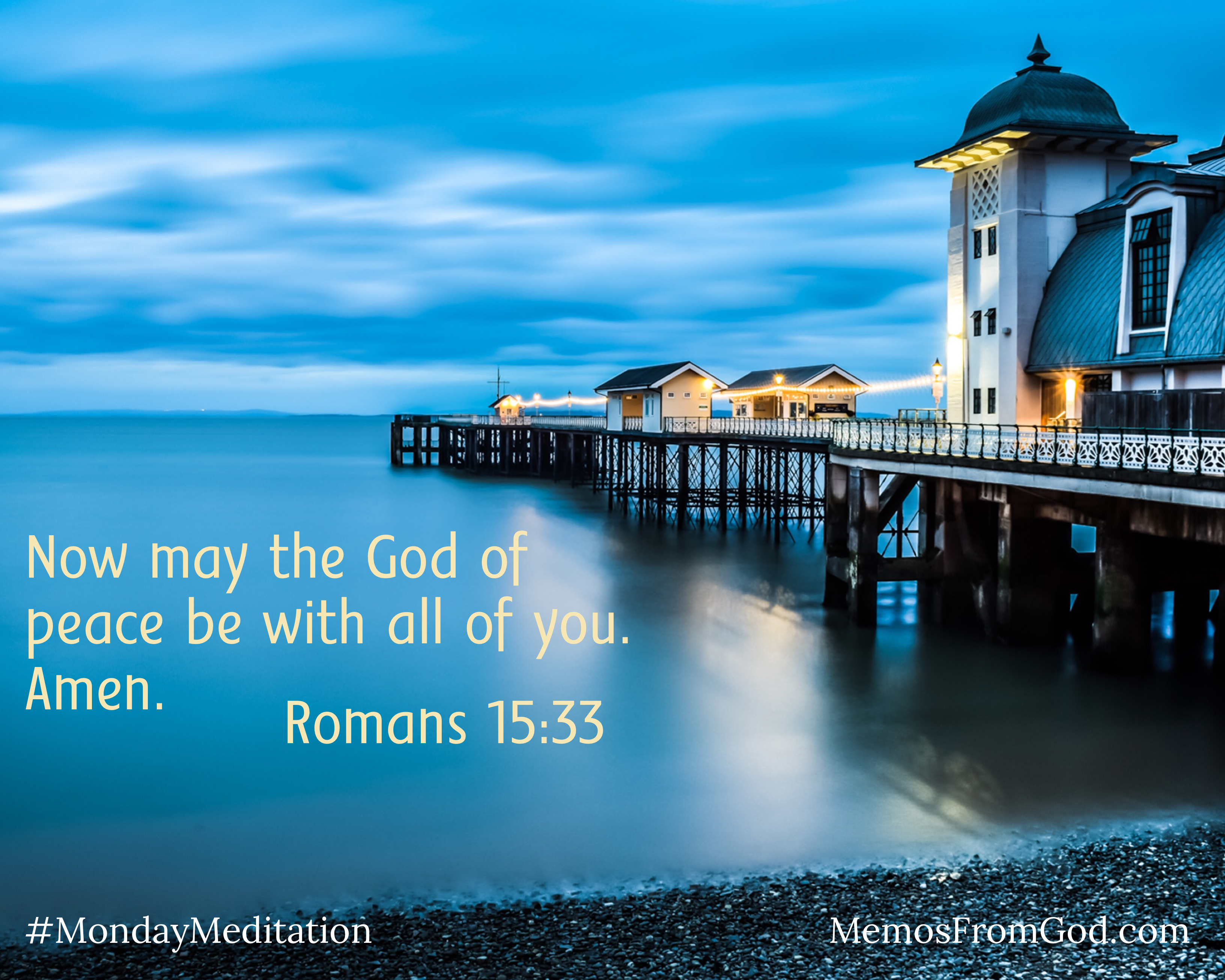 An evening sky is full of clouds. Glowing, golden lights shine from buildings on a pier that extends into a dark blue lake that is as smooth as glass. Caption: Now may the God of peace be with all of you. Amen. Romans 15:33